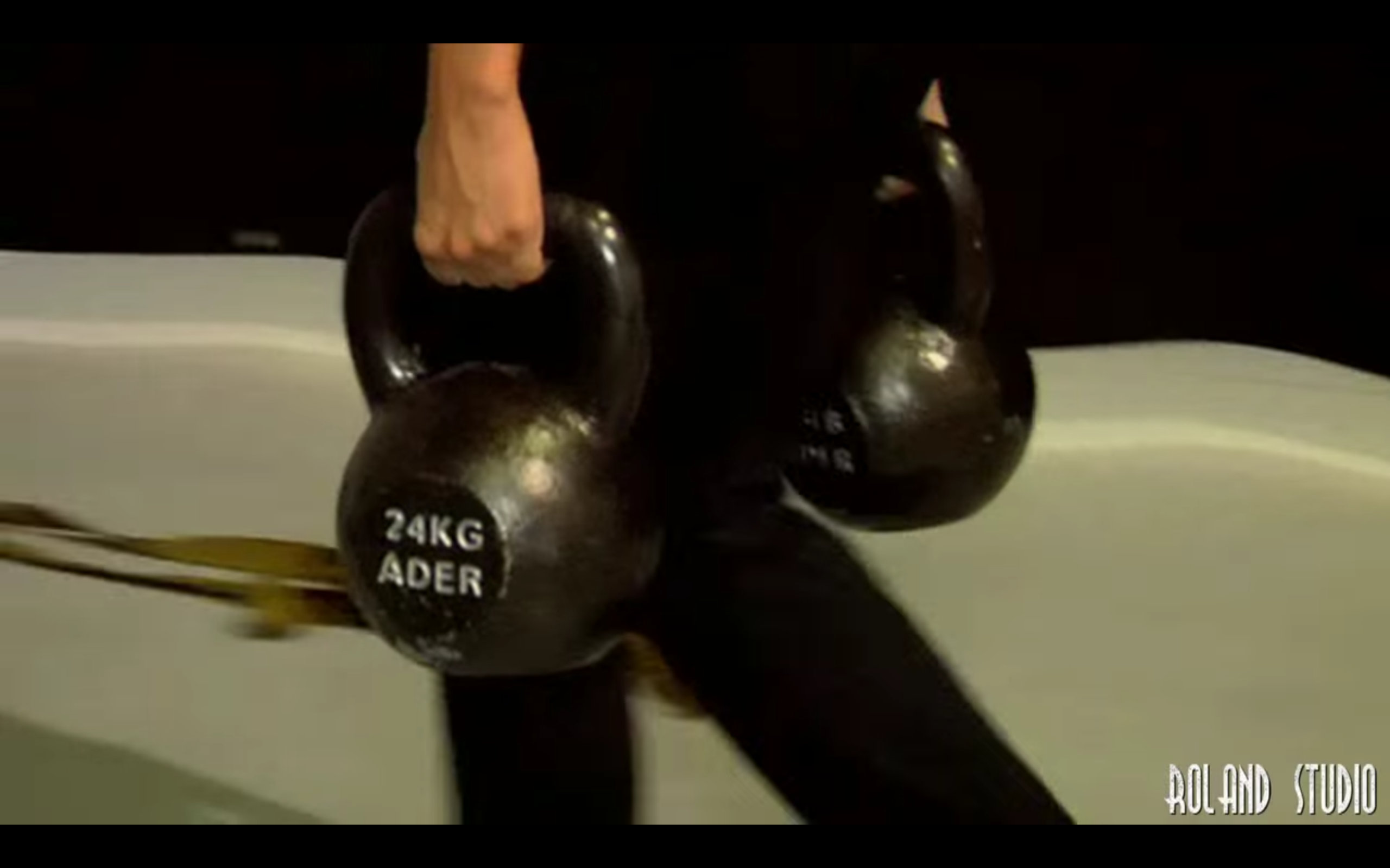 Vanessa farmer's carrying two 24kg (53 pound) kettlebells, from the Sucker Punch DVD Extraas